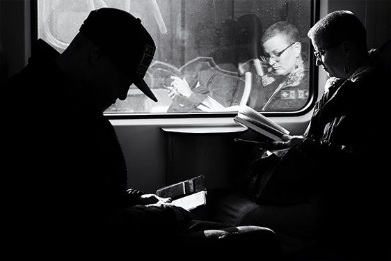 Street photographer friso kooijman fotograaf Amsterdam Nederland Netherlands zwart wit black white fotograaf train reading telephone book reflection